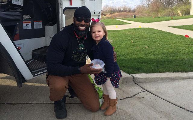 Klein meisje verrast favoriete vuilnisman met verjaardagscupcake