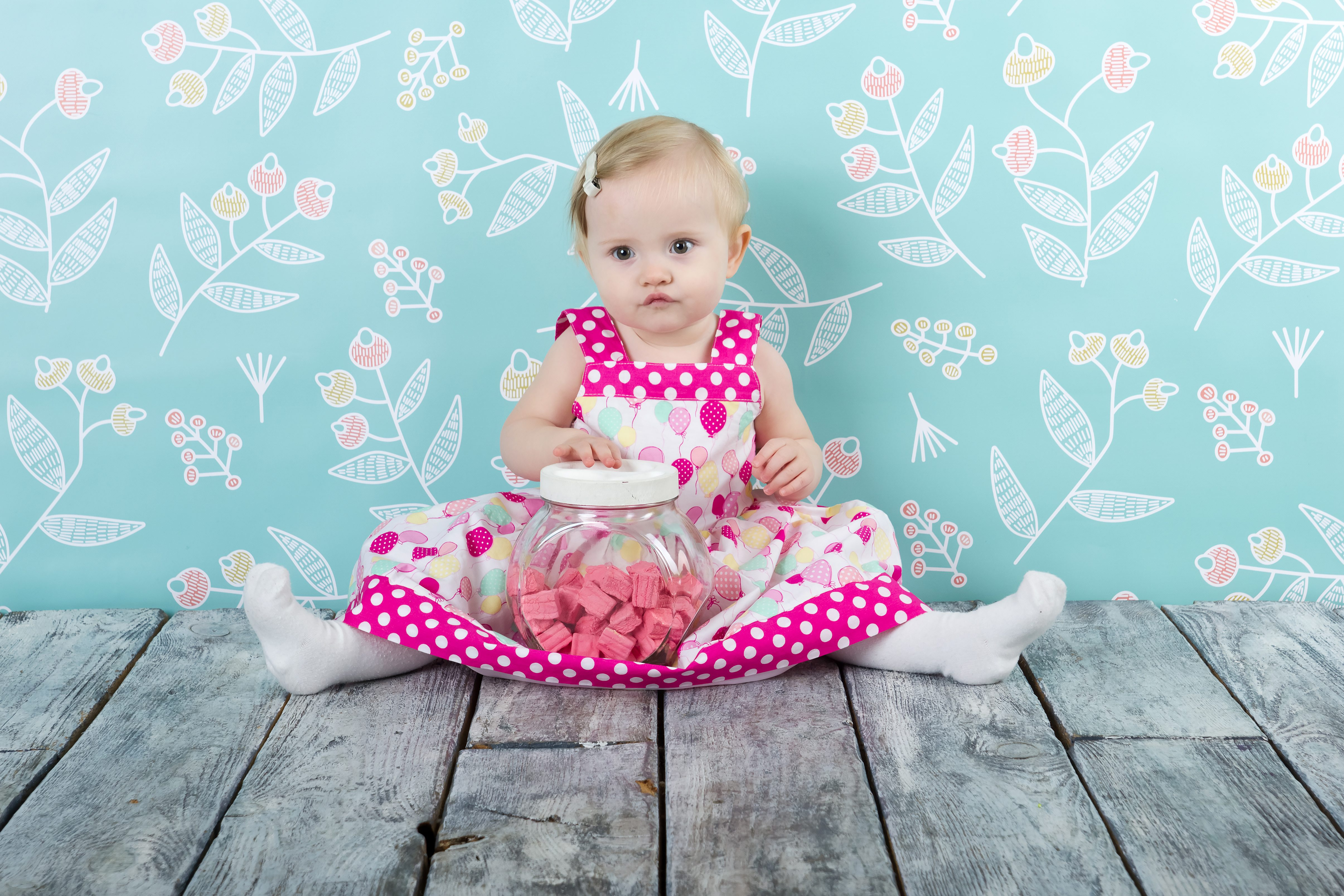 Girl in pink dress sitting on the wooden floor with candy jar on blue flower background holding a toy.; Shutterstock ID 234210592; Title: meisjesnamen uit natuur