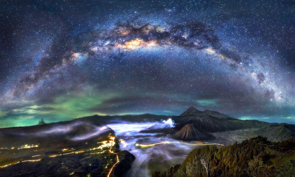 PIC BY STEVE LANCE LEE/CATERS NEWS - (PICTURED: The incredible Milky Way over Mount Bromo, Probolinggo, Indonesia) - These stunning pictures showing the Milky Way over a volcano will take your breath away. The midnight blue sky is lit up with green and orange hues, as the glittering stars form a beautiful arch over volcanoes. The amazing pictures were snapped by photographer Steve Lance Lee, around Malaysia and East Java Indonesia. SEE CATERS COPY.
