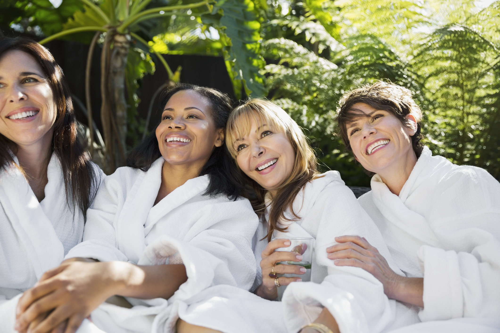 Smiling women in bathrobes sitting at health spa