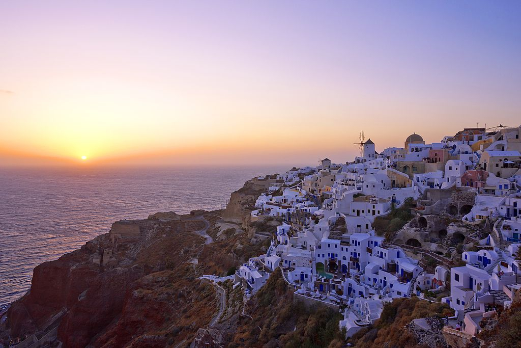 Greece, Cyclades, Santorini Island, Oia, View of Santorini Island and windmill at sunset. (Photo by: JTB Photo/UIG via Getty Images)