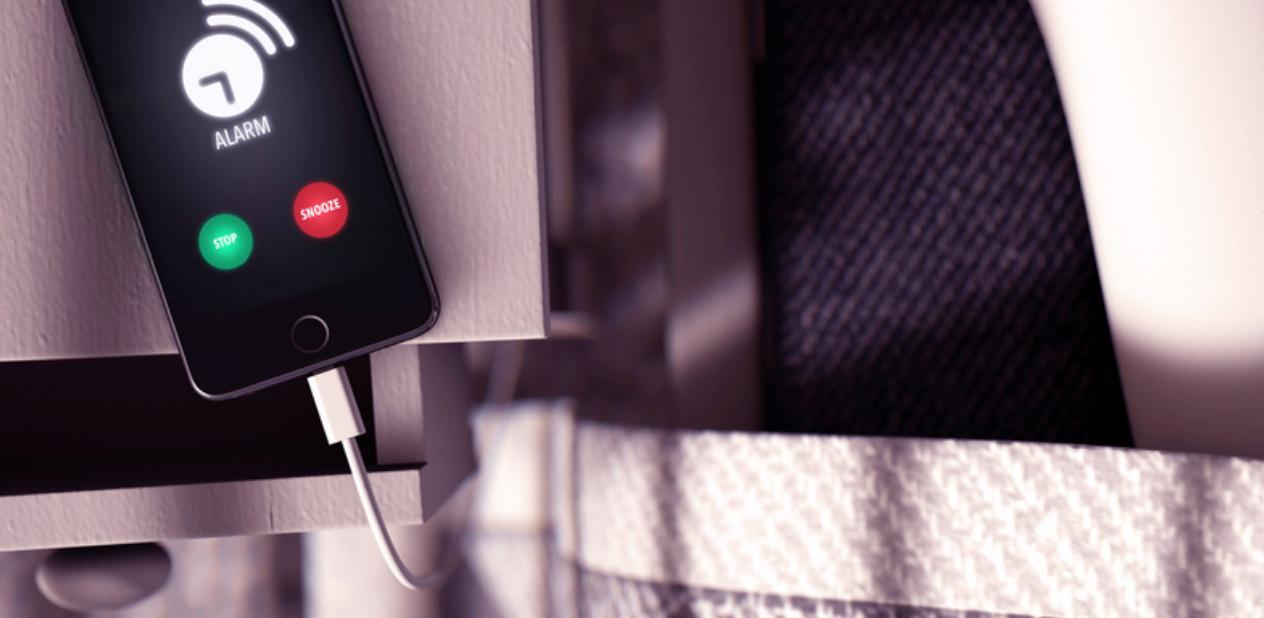 Waarom je je telefoon nóóit naast je in bed moet opladen